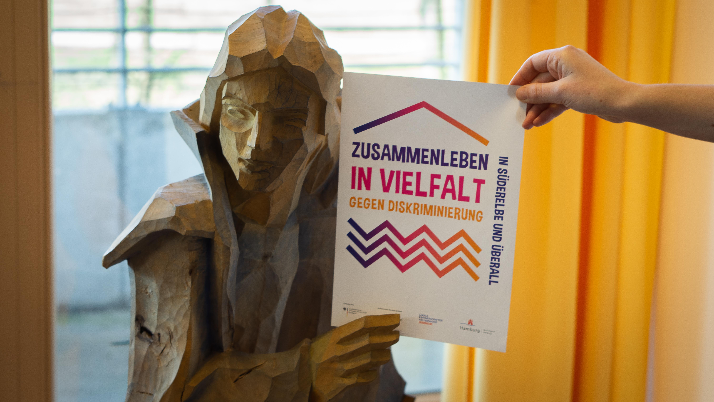 """Der Zettel """"Zusammenleben in Vielfalt"""" wird von einer geschnitzten Menschenskulptur und einer Hand ins Bild gehalten."""