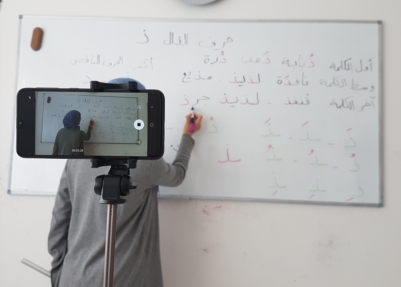 Eine Frau steht vor einem Whiteboard und schreibt in arabischer Sprache. Im Vordergrund steht eine Handykamera auf einem Stativ durch die, der Ausschnitt mit der Frau vor dem WhiteBoard aufgezeichnet wird.
