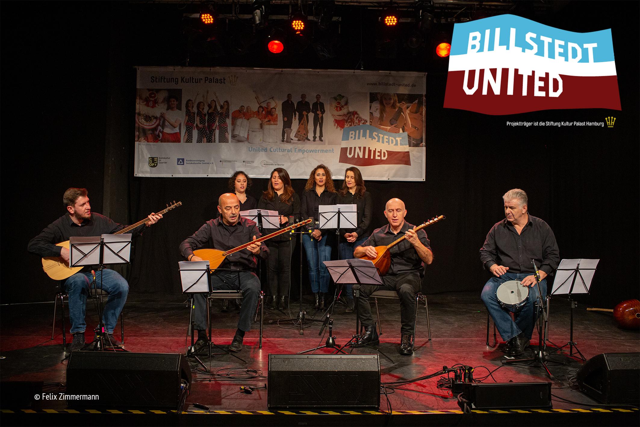 Vier Männer spielen im Vordergrund sitzend auf Zupfinstrumenten, im HIntergrund stehen vier Frauen und singen. Sie schauen paarweise in ihre Noten