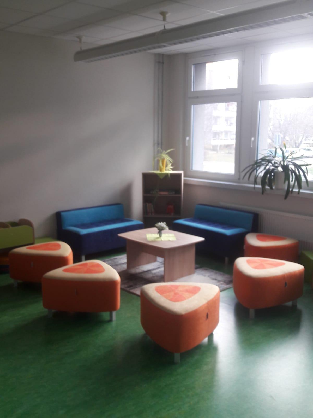 Gemütliche Sitzecke mit Hockern und Sofas im Kreis gestellt, vor einer Fensterfront