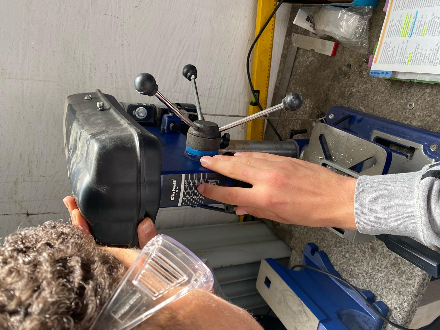 Einem Jugendlichen, mit Schutzbrille an einer Werkbank stehend und an einer Maschine arbeitend, wird von hinten über die Schulter geschaut.