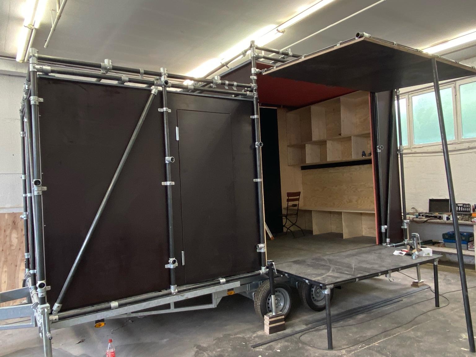 Der mobile Bauwagen, von der Seite fotografiert, steht in einer Werkstatt. Der Bauwagen ist an der Seite nach oben aufgeklappt, sodass man hinein schauen kann.