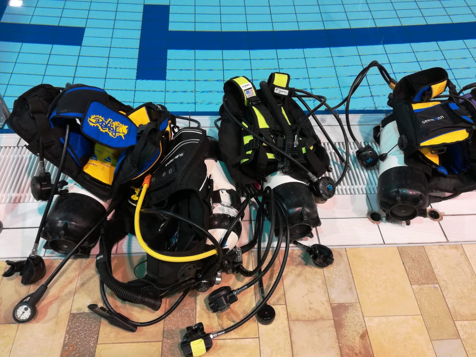 Drei Taucherausrüstungen (Sauerstoffflasche mit Oberkörperweste) liegen am Schwimmbadbeckenrand.