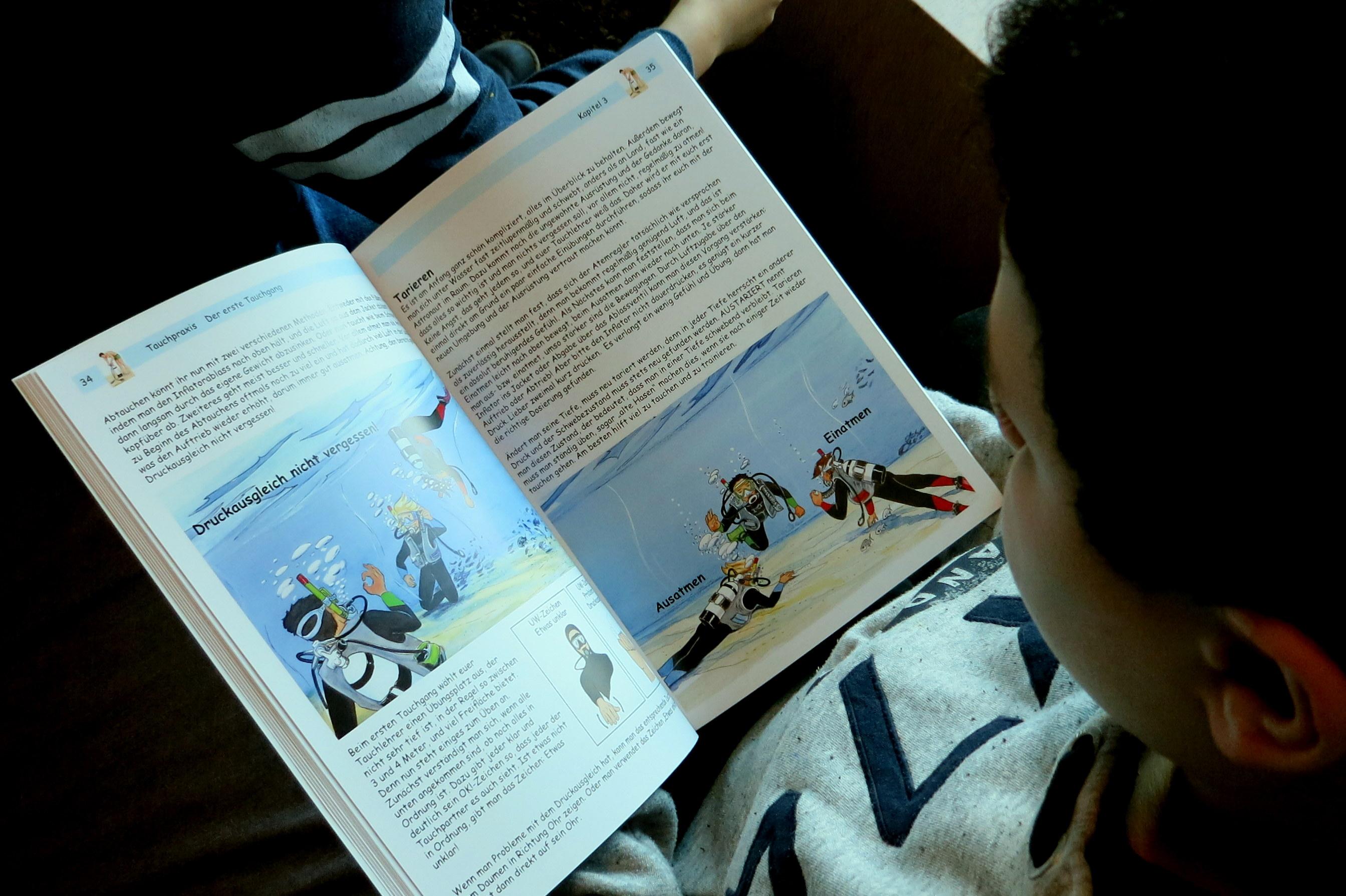 Auf dem aus Vogelperspektive aufgenommenem Foto sitzt ein Jugendlicher mit einer kindgerechten Fachliteratur zum Thema Tauchen in der Hand.