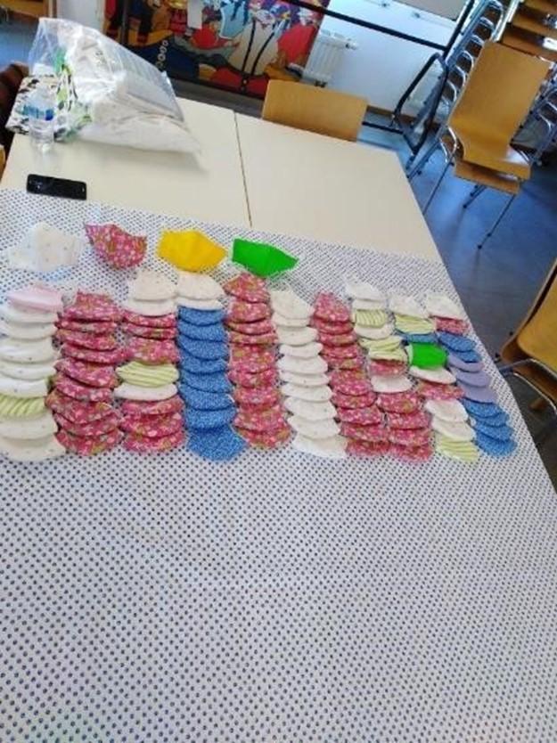 Zahlreiche, verschiedenfarbige Behelfsmasken liegen auf dem Tisch ausgelegt.