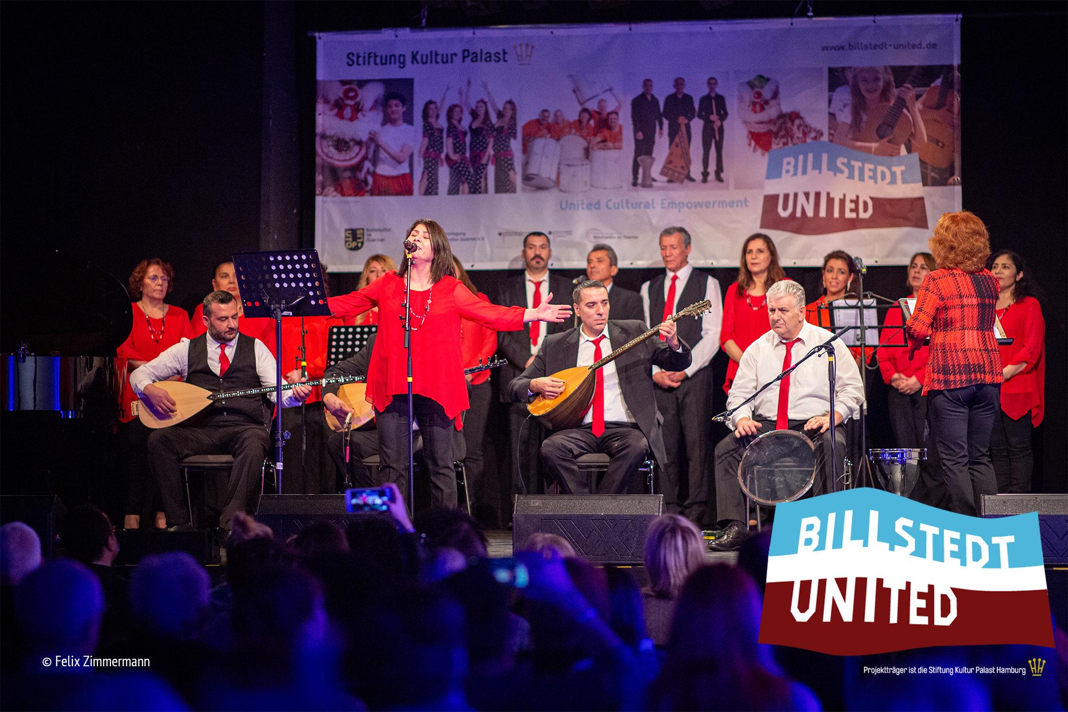 Eine Sängerin in rot steht vor einer Musikgruppe von vier Personen, die im Halbkreis sitzen. in der hinteren Reihe steht ein Chor von rd 12 Personen. SIe sind alle in rot und schwarz TÖnen gekleidet. Die SÄngerin hat die AUgen geschlossen und die Arme ausgebreitet