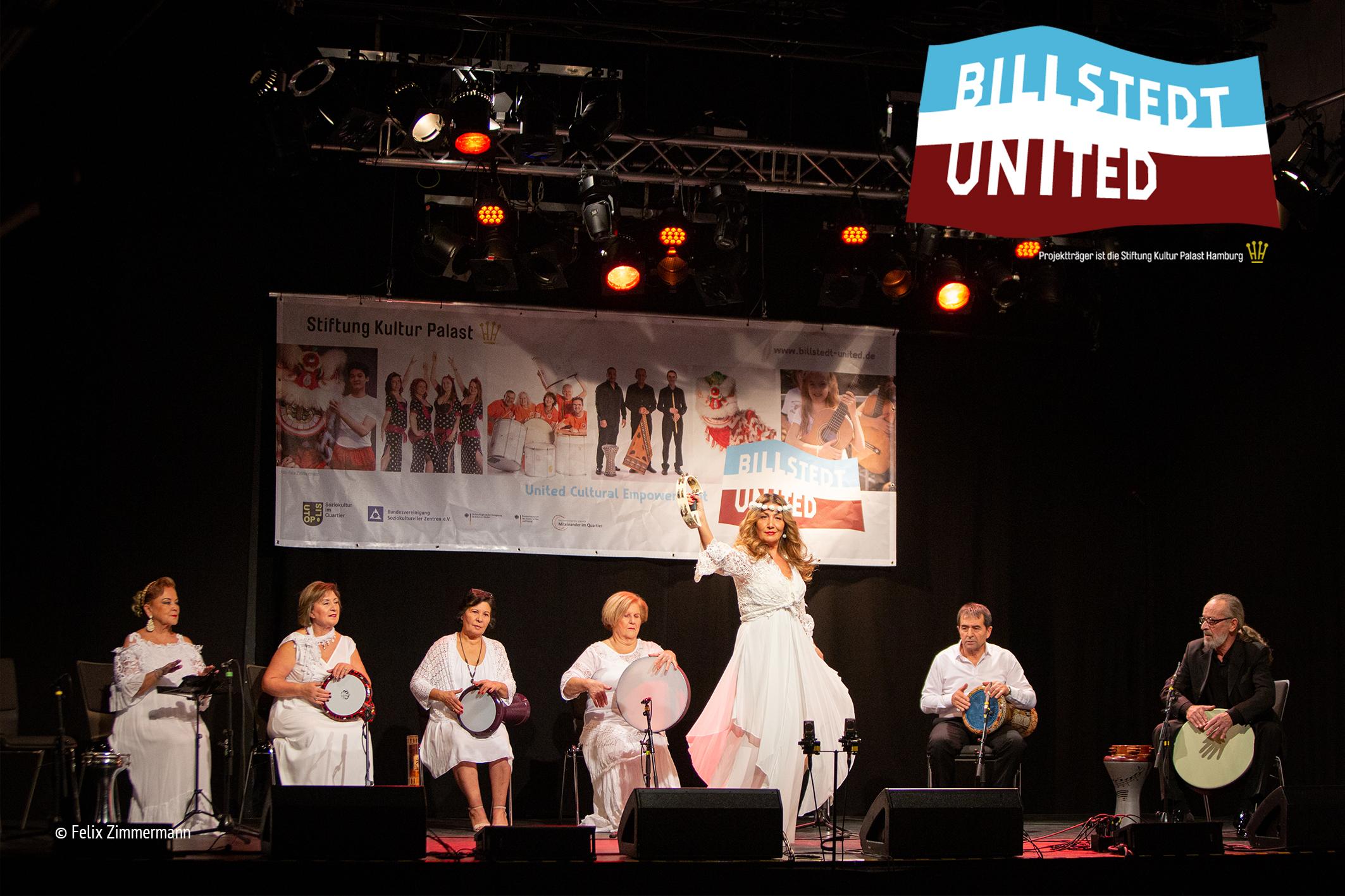 Sieben Männer und Frauen sitzen auf einer Bühne im Halbkreis und spielen unterschiedliche Rhytmusinstrumente. Fast alle haben rein weiße Kleidung an. Im Vordergrund steht eine blonde Frau im weißen Kleid und roten Lippenstift, die ein Tamburin in die Luft streckt