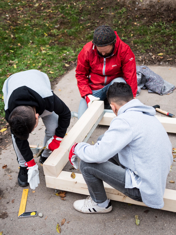 Holzbalken werden von drei Personen auf dem Fußboden vermessen und miteinander befestigt.