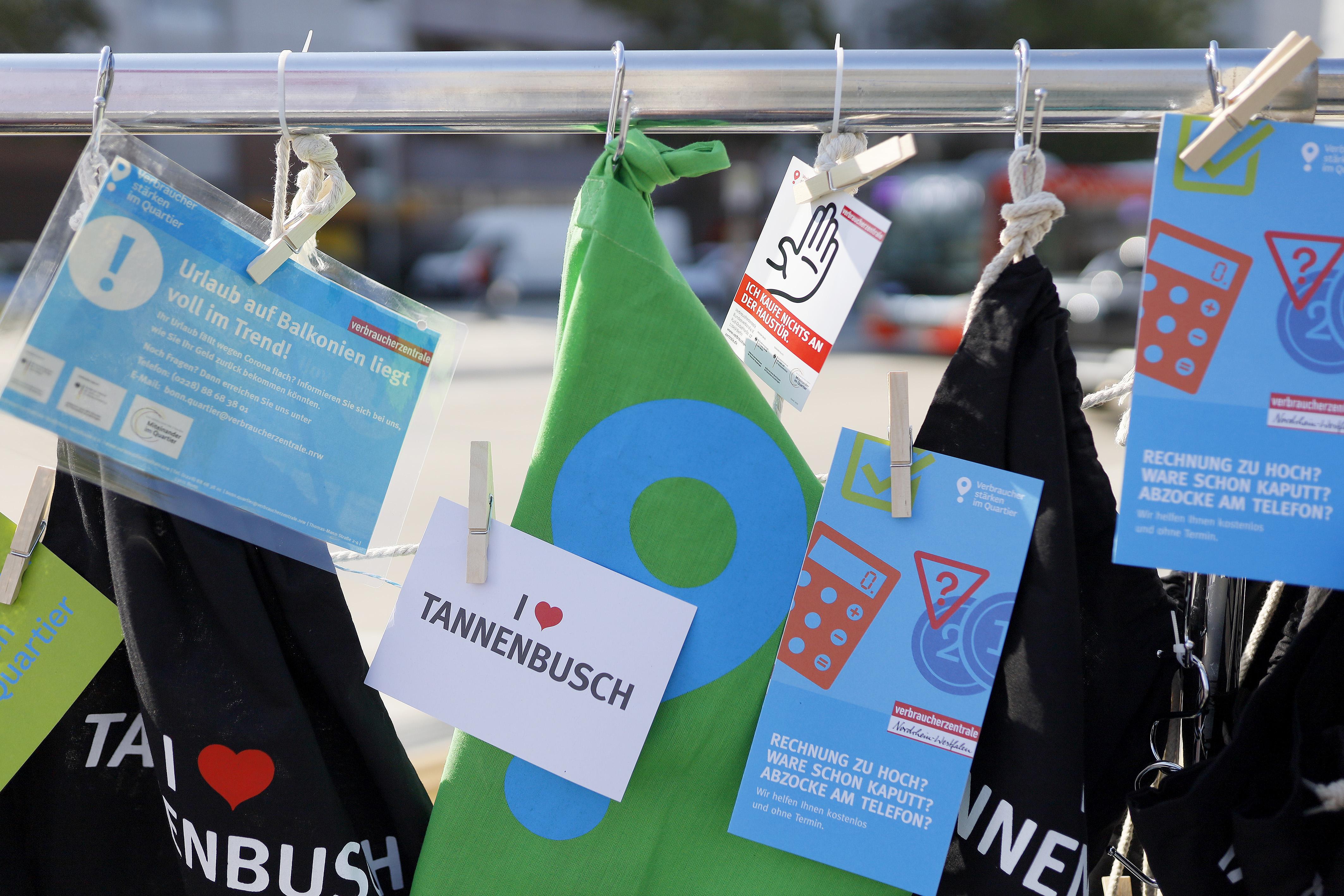 Flyer, Poster und Stoffbeutel der Verbraucherzentrale hängen an einer Stange.