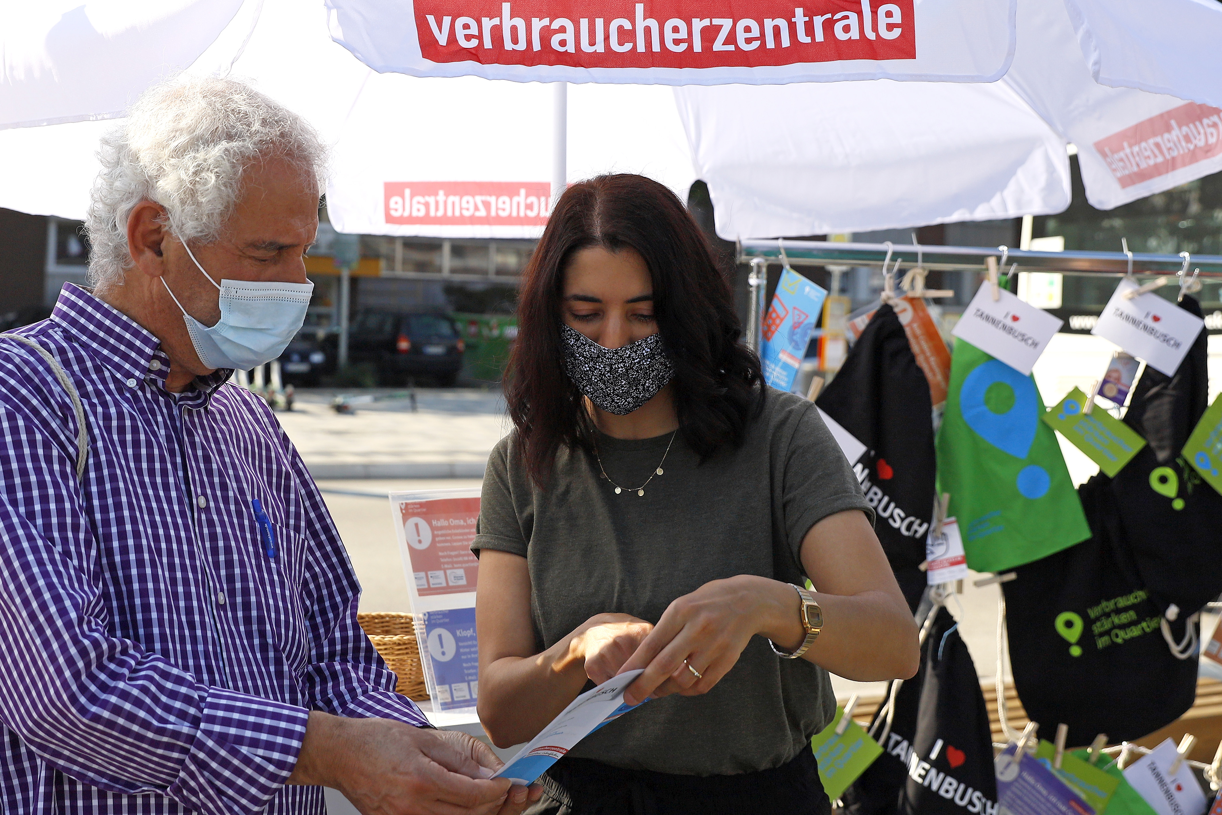 Eine junge Frau zeigt einem älteren Herren einen Flyer.