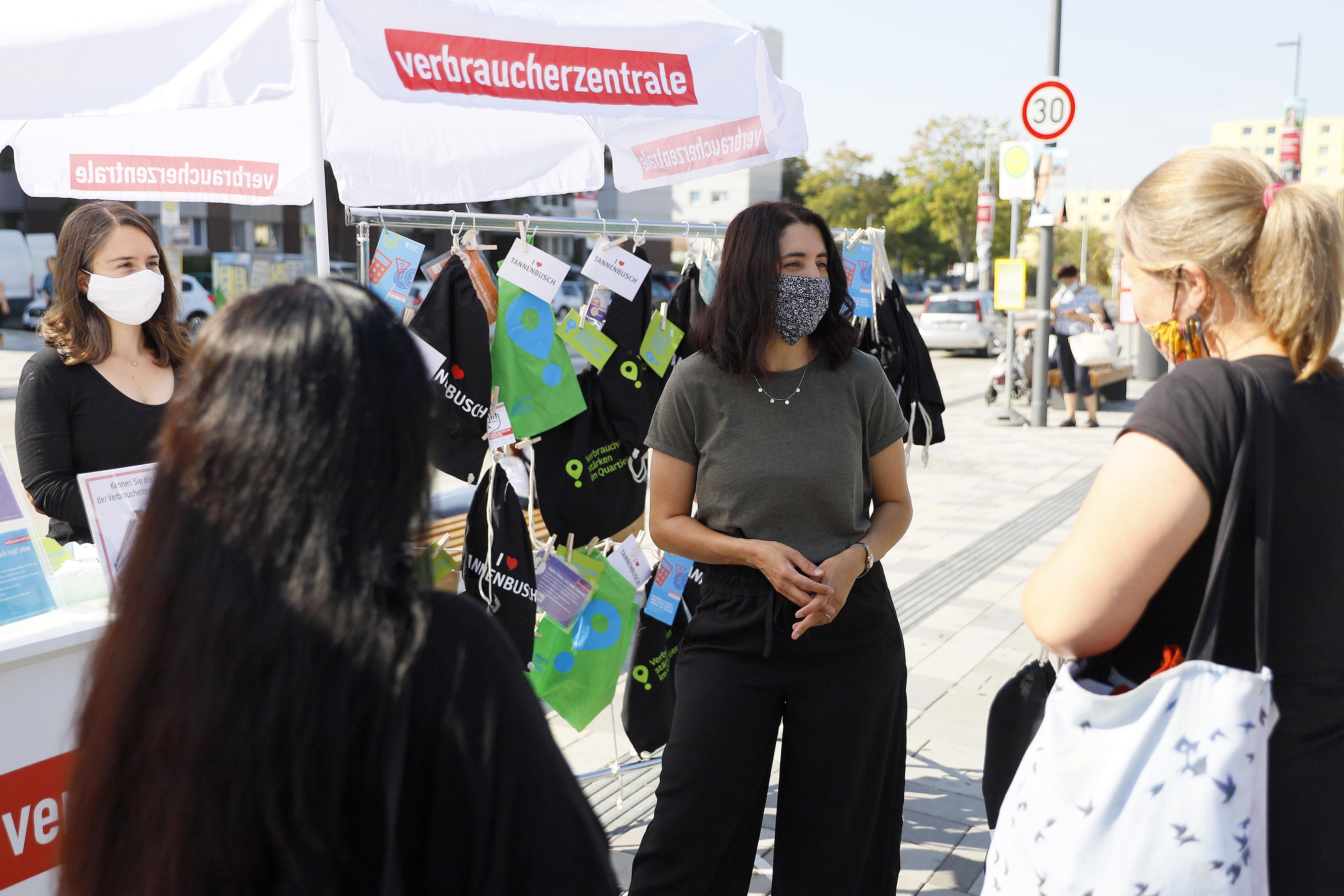Zwei Frauen der Verbraucherzentrale kommen vor dem Infostand mit zwei Personen ins Gespräch.