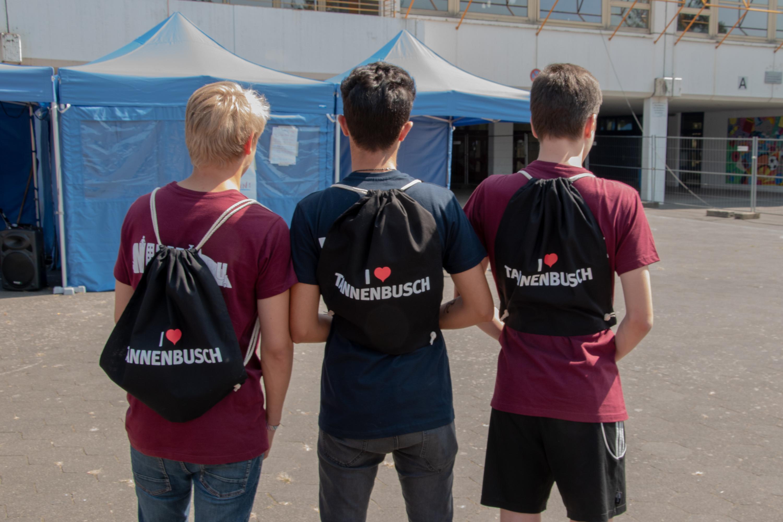 """Drei Jugendliche, mit dem Rücken zur Kamera, tragen einen Jutebeutel mit der Aufschrift """"I ♥ Tannenbusch""""."""