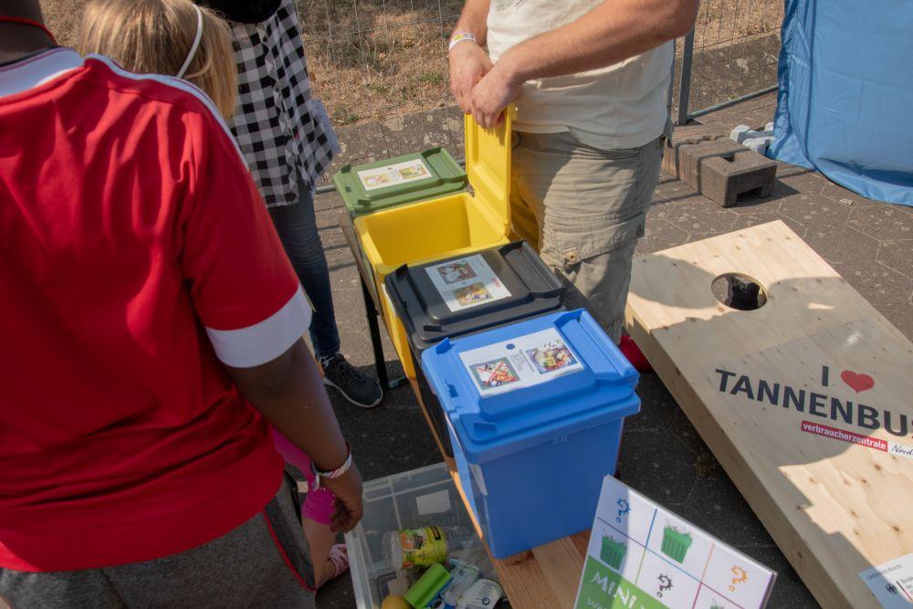 Jugendliche stehen vor einer Sitzgarnitur, auf der Mini-Mülltonnen mit Infozetteln aufgestellt sind.
