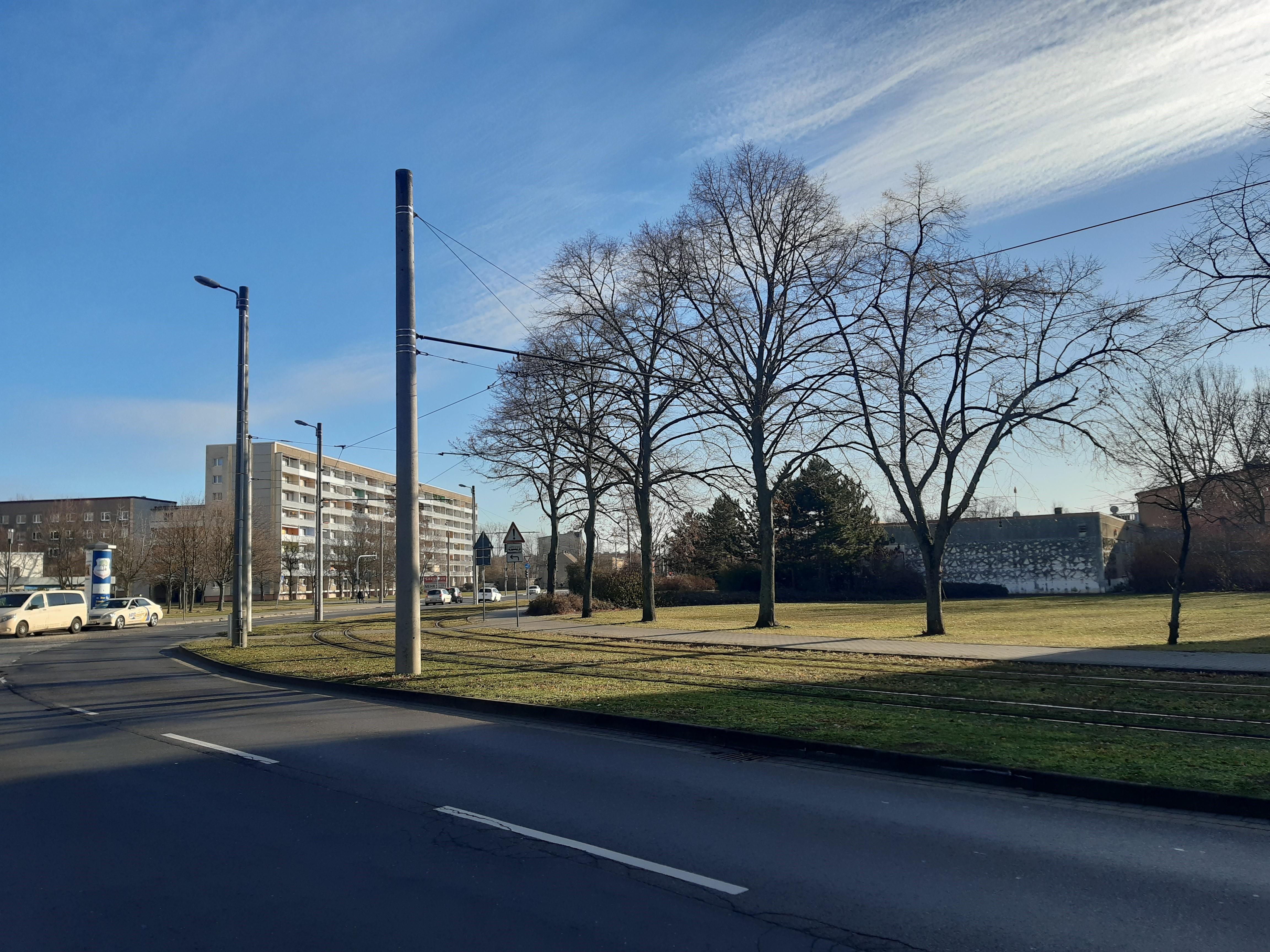 Blick auf Quartier: Autostraße, daneben Straßenbahnspuren, im Hintergrund Wohnblocks