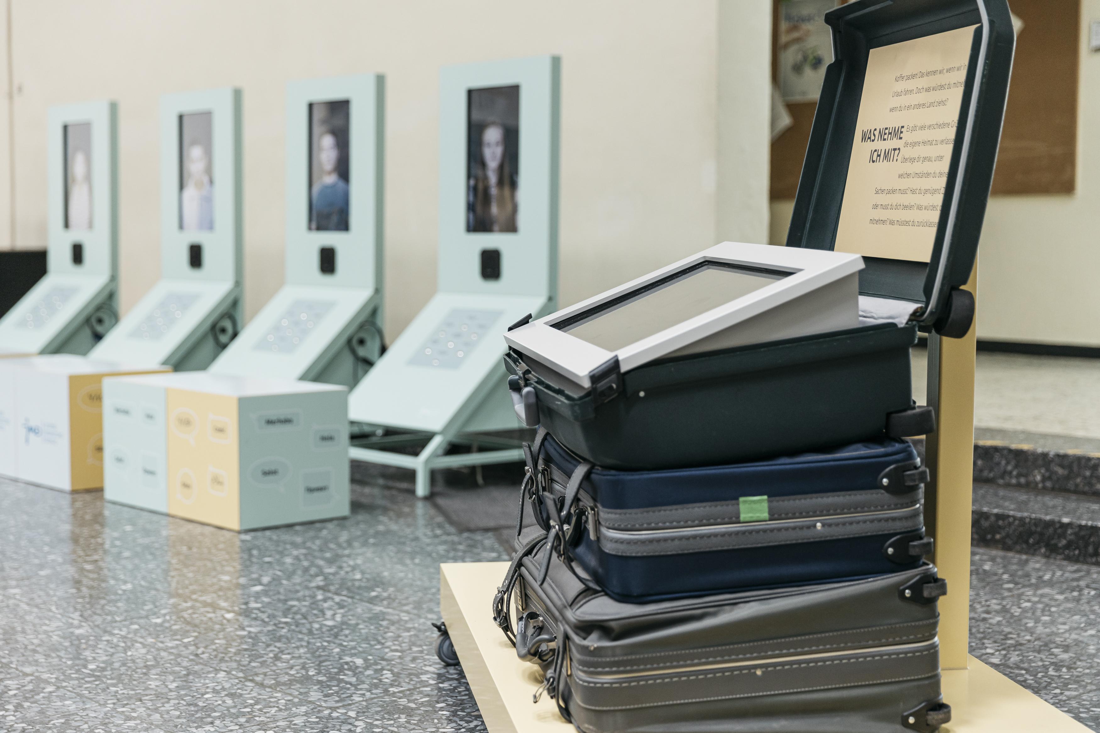 Ein Teil der Ausstellung mit einem Display auf gestapelten Koffern zur Frage: Was nehme ich mit?