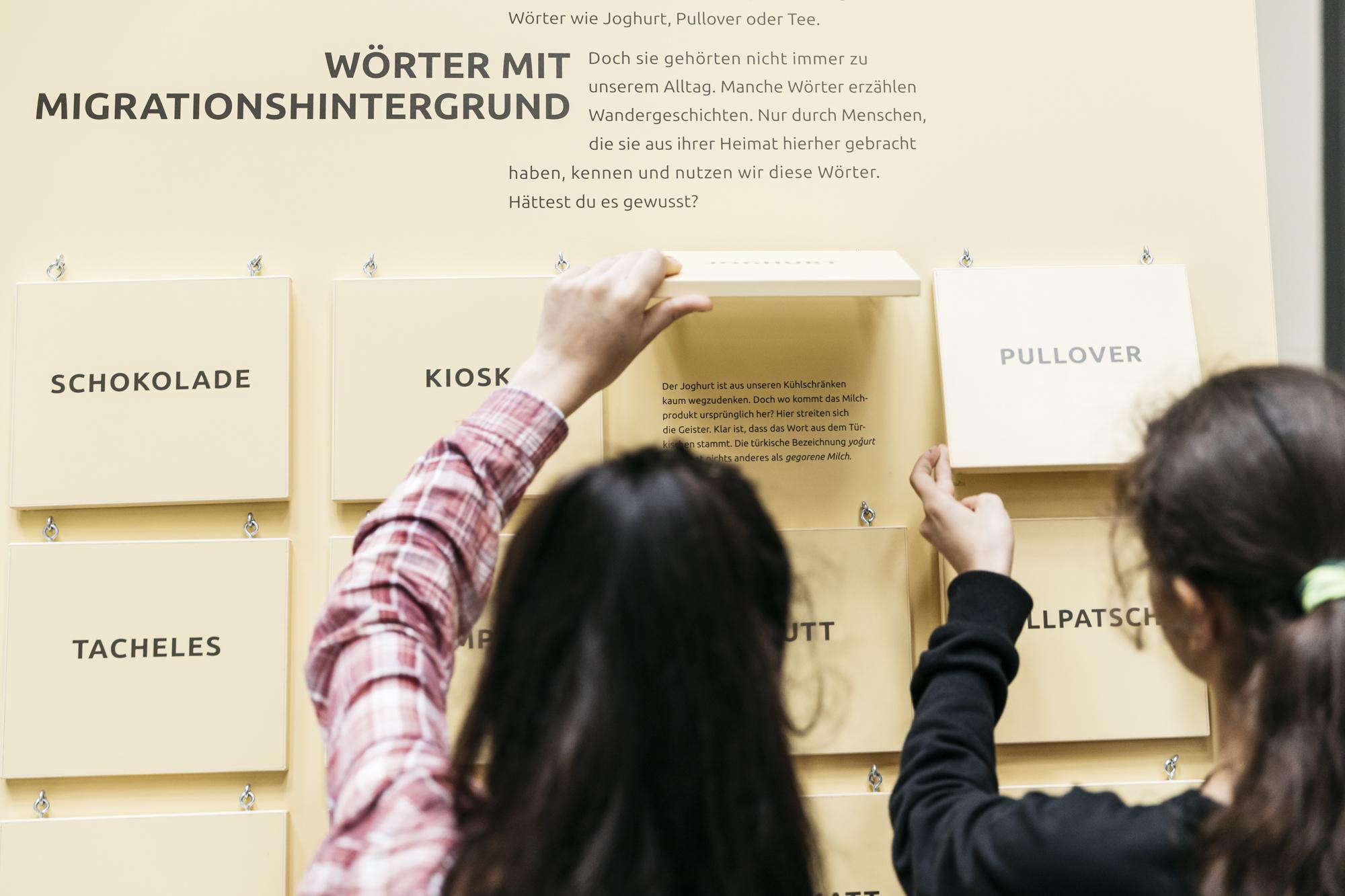 Zwei Jugendliche stehen vor einer interaktiven Ausstellungswand, bei der es um Wörter mit Migrationshintergrund geht.