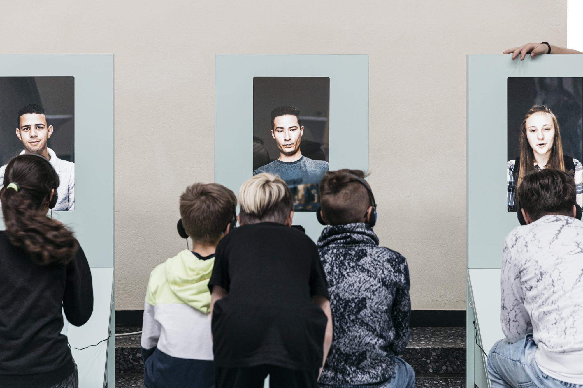 Jugendliche sitzen, mit Kopfhörern auf, nebeneinander und schauen auf drei Austellungsmodelle.