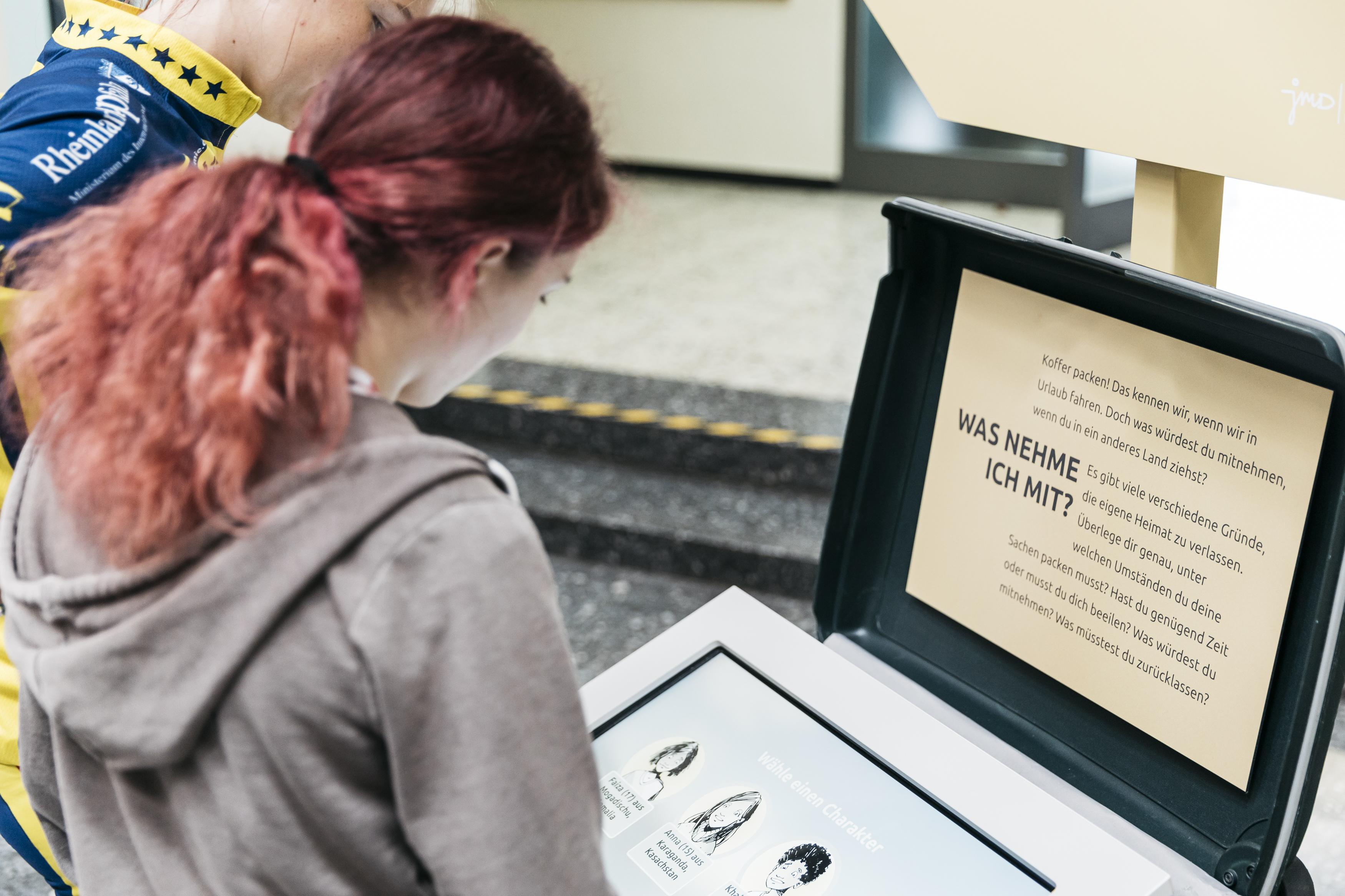 Zwei Junge Menschen stehen vor einem interaktivem Display zur Frage: Was nehme ich mit?