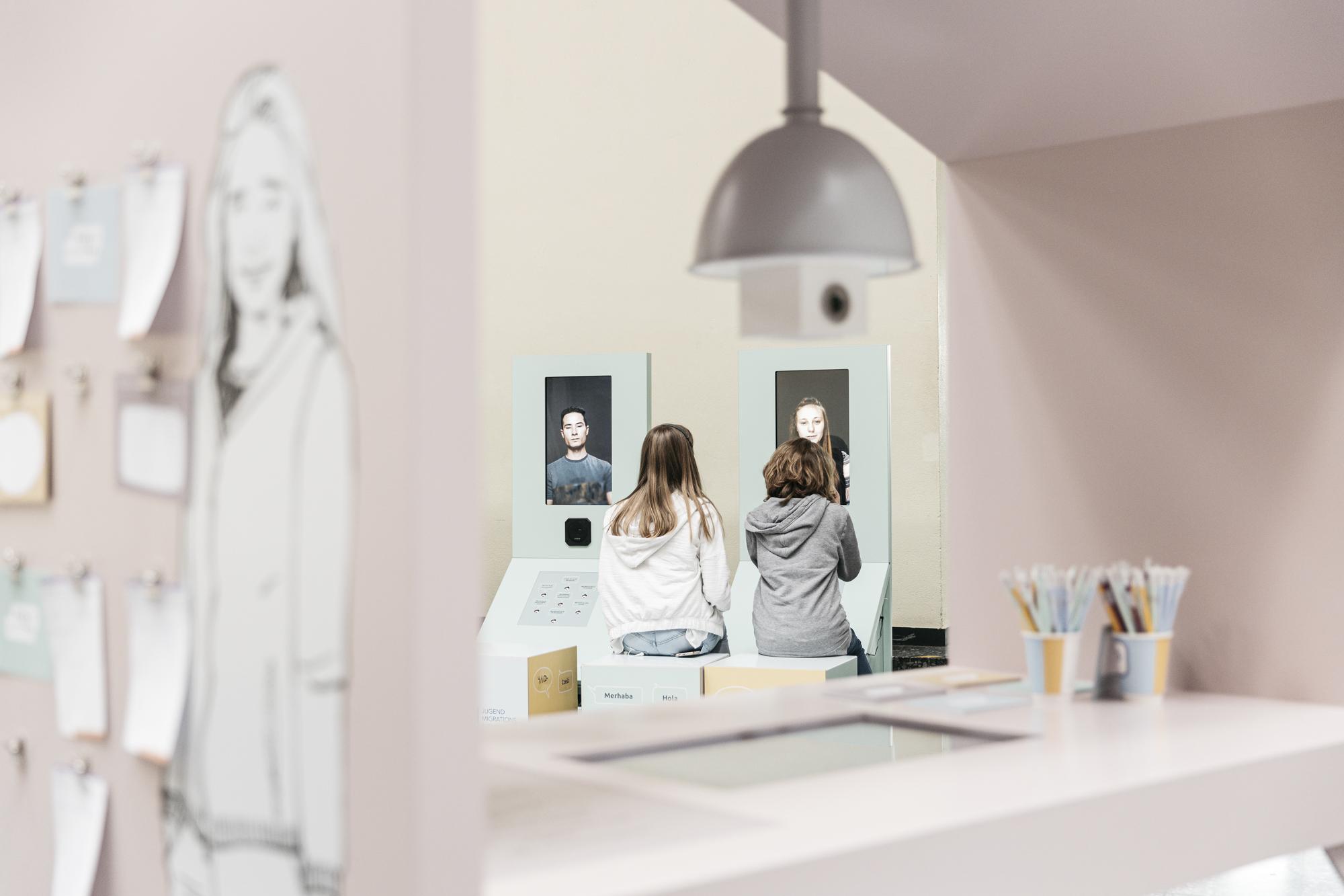 Zwei Mädchen sitzen nebeneinander auf Hockern an einem interaktiven Ausstellungsstück.