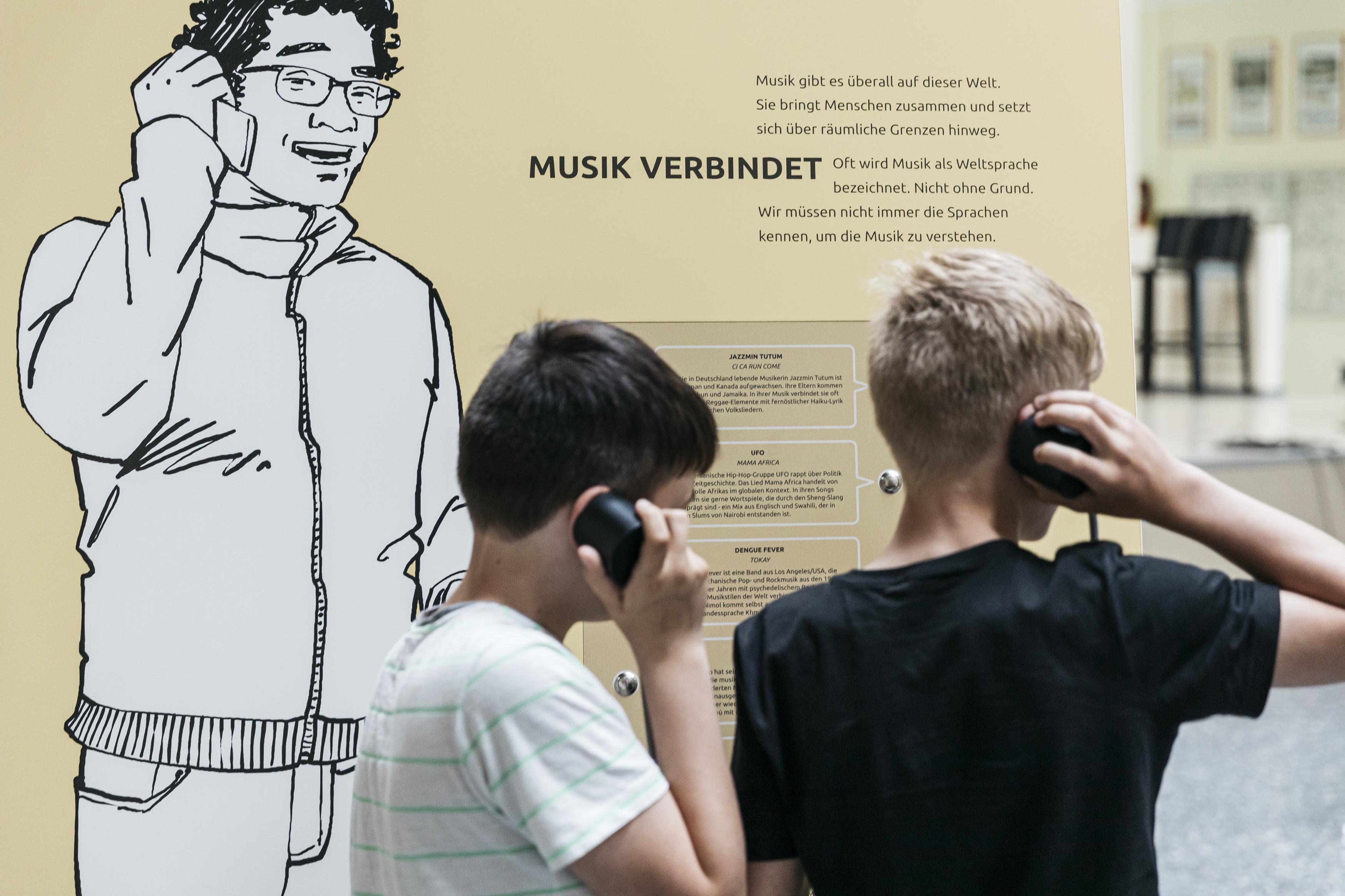 """Zwei Jungen stehe vor der Ausstellungswand """"Musik verbindet"""" und haben jeweils einen Hörer am Ohr."""