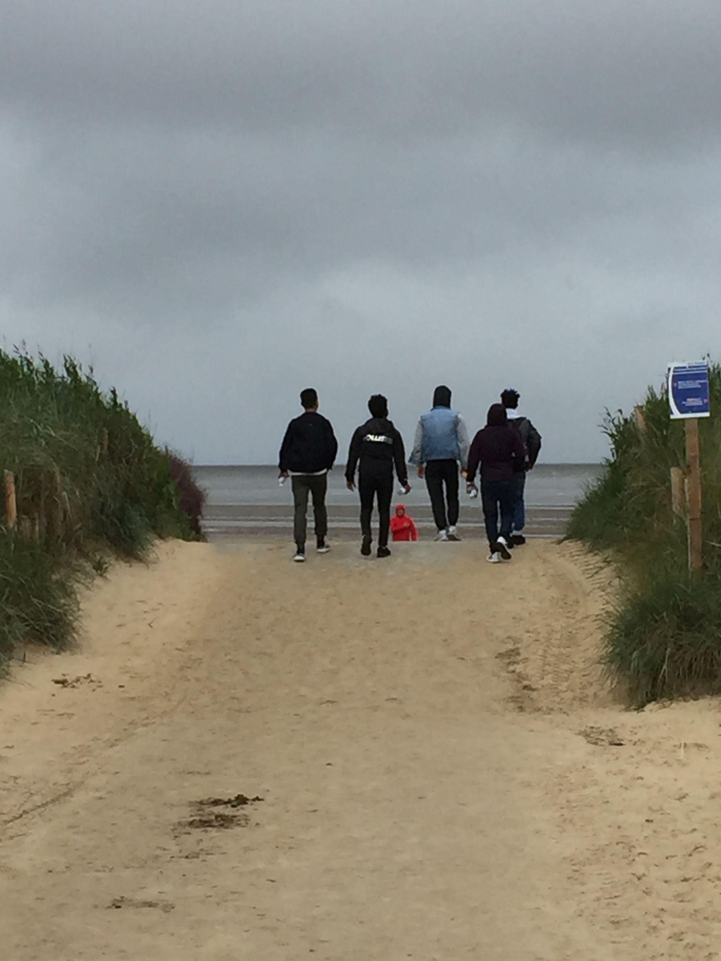 Vier Jugendliche, von hinten zu sehen, laufen auf einem Strandweg zwischen den Dünen bei bedecktem Wetter zum Meer hinunter.
