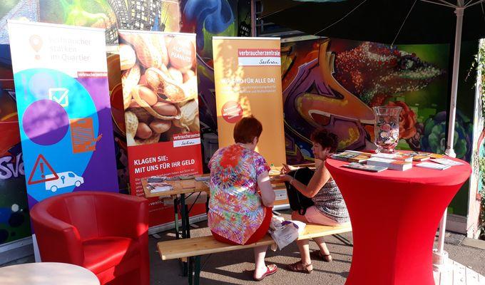 Zwei Frauen sitzen bei dem Infostand des Verbraucherschutzes auf einer Bank und unterhalten sich.