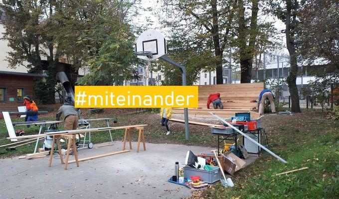 Sechs Personen bauen hinter einem Basketballfeld eine Tribüne. Viele Werkzeuge und Holzteile sind verstreut. Auf dem Bild steht mit gelber Markierung: #miteinander.