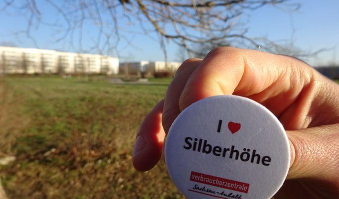 Eine Hand hält einen weißen Button mit der Aufschrift I Love (Herz) Silberhöhe. Im Hintergrund ist ein Feld und ganz entfernt eine Reihe Hochhäuser