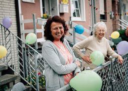 Zwei Omas lachen und stehen hinter einem Zaun in ihrem Vorgarten. Um sie herum sind viele bunte Ballons angebracht.