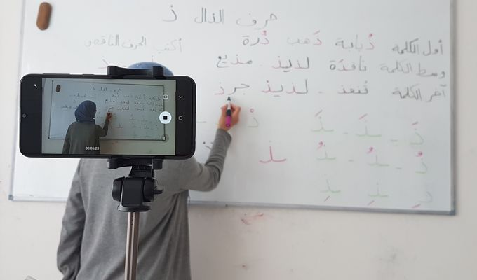 Eine junge Frau mit Kopftuch wird von einem Handy gefilmt. Sie schreibt in bunter Schrift arabische Wörter auf ein Whiteboard.