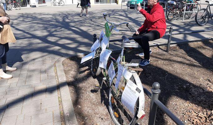 Fahrrad mit Infozetteln an Zaun gelehnt. Daneben sitzt ein Mann und spricht mit Bewohnerin.