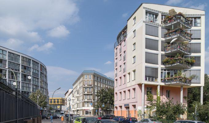 Straßenzug in Berlin-Moabit, Häuser sind verschiedenen Baualters. Der Himmel ist blau.