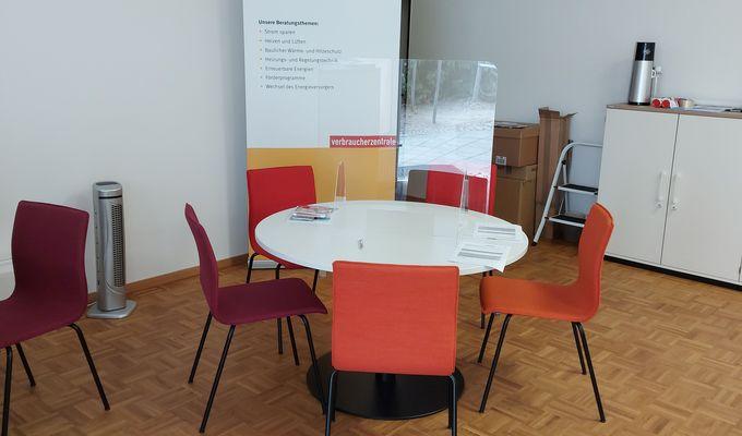 rote und orangene Stühle stehen um einen runden weißen Tisch. Im Hintergrund steht in der Raumecke ein Roll up mit Informationen der Verbraucherzentrale. Der Raum ist weiß gestrichen und wirkt leer.