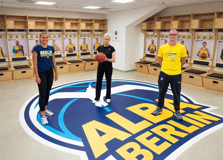 Die beiden Jugendtrainer und Staatssekretärin Anne Katrin Bohle stehen in der Mannschaftsumkleide von Alba Berlin.