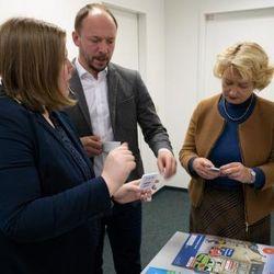 Drei schick gekleidete Personen halten Karten in den Händen und diskutieren.
