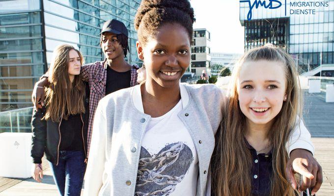 Zweimal zwei Jugendliche unterschiedlicher Hautfarbe laufen Arm im Arm und lachen zusammen.