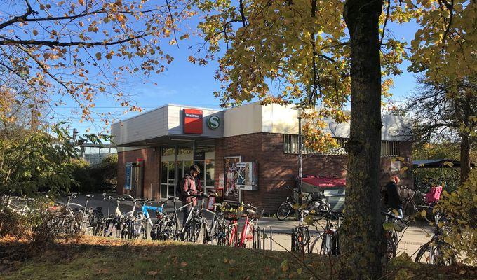 Eine S-Bahnstation mit vielen Fahrrädern. Ringsherum stehen Bäume und Büsche mit gelbem Laub. Der Himmel ist blau.
