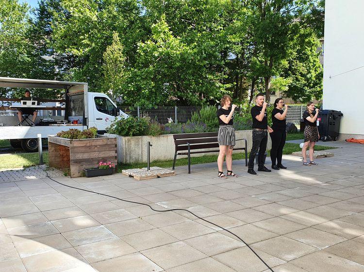 Vier Personen stehen nebeneinander auf eine Platz und singen. Sie tragen alle schwarze Klamotten. Links im Hintergrund steht ein Lastkraftwagen. Auf der Ladefläche sitzt ein Mann und spielt Klavier.