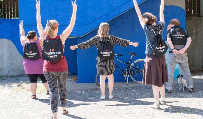 Fünf Personen stehen mit dem Rücken voran und tragen schwarze Jutebeutel. Sie strecken ihre Arme auseinander. Auf den Beuteln steht: Ich liebe Oggersheim-West.
