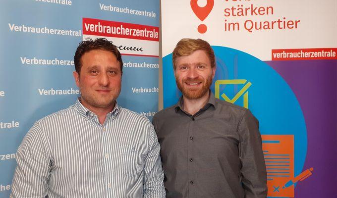 Zwei Mitarbeiter im Schweizer Viertel stehen vor Stellwänden des Verbraucherschutzes.  Beide lächeln. Der linke Mann trägt ein weiß-grau gestreiftes Hemd, der rechte Mann trägt ein dunkelgraues Hemd.