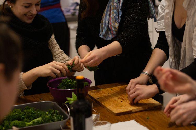 Eine Gruppe Frauen kochen und unterhalten sich.