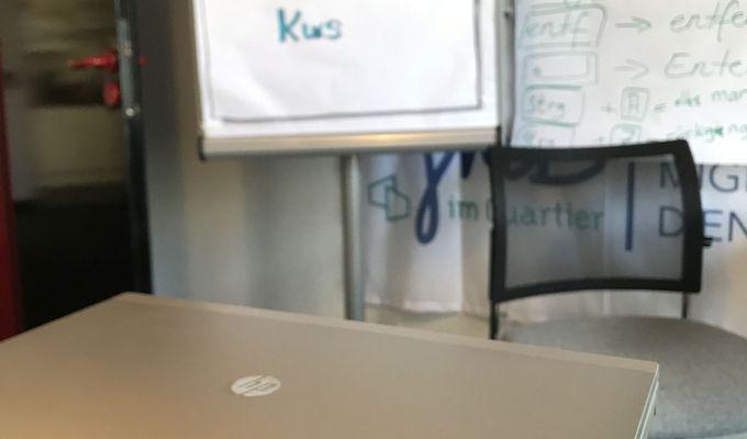 """Zwei Laptops liegen übereinander auf einem Tisch. Im Hintergrund steht eine Flipchart aufgestellt mit den Worten: """"Herzlich Willkommen zum COMPUTER Kurs""""."""