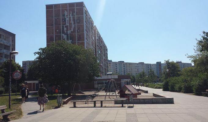 In einem Wohngebiet stehen Hochhäuser. Im Vordergrund ist ein Spielplatz mit Bäumen und einigen Spaziergängern.