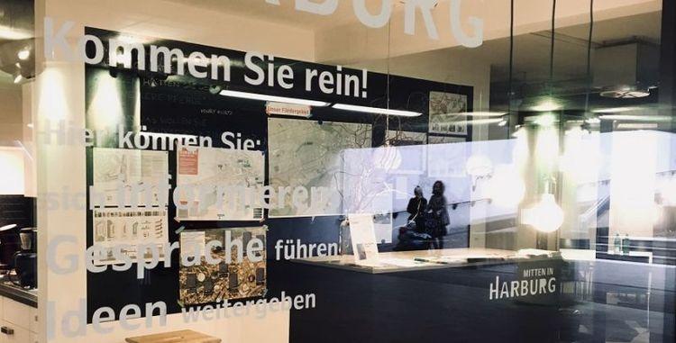 Ein verglaster Raum mit Informationsstand. An der Glaswand stehen Anregungen, die zum Eintreten animieren sollen. Im Raum an der Wand hängen Landkarten.
