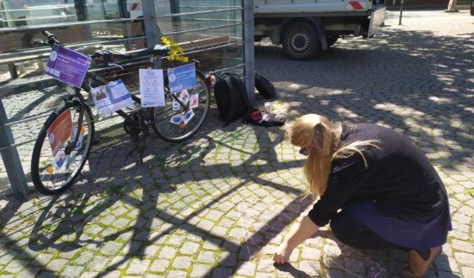 Das Info Fahrrad steht vor einem Sportplatz. Die betreuende Mitarbeiterin knieht davor und malt mit Kreide etwas auf den Boden