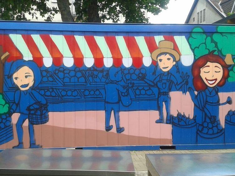 Eine besprühte Wand, auf der gezeichnete, glückliche Menschen beim Lebensmittel mitnehmen zu sehen sind.