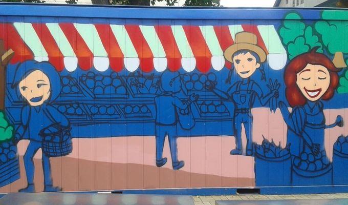 Auf eine Wand wurden lächelnde Menschen beim Lebensmittel Einkaufen gezeichnet. Der Großteil des Bildes ist blau.