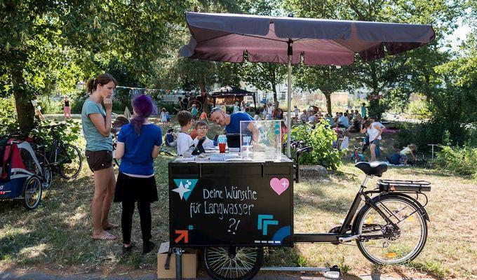 Das Lastenfahrrad, an dem die Bürger ihre Wünsche mitteilen können steht im Park. Darum herum verteilt stehen Kinder, der Betreuer des Standes und eine Frau.