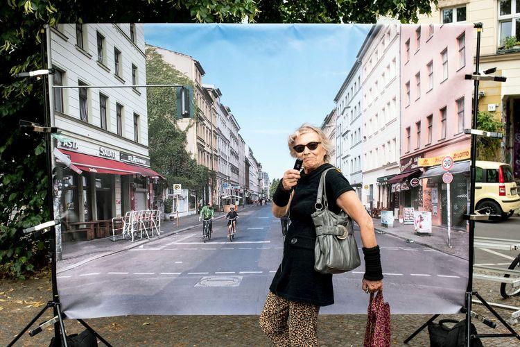 Eine hippe Oma trägt eine Sonnenbrille und posiert vor einer Fotoleinwand. Das Foto ist aus einer Drittperspektive aufgenommen und zeigt eine Straße mit Fahrradfahrern.