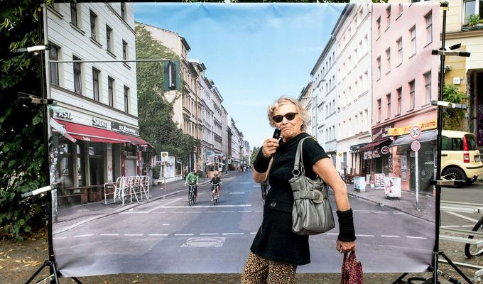Coole Kreuzberger Oma posiert vor der Leinwand. Sie trägt eine graue Handtasche über der Schulter und Hosen mit Leopardenprint.